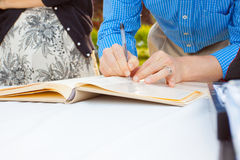 Signing a Guestbook. A man and a woman sign a wedding guestbook with a pen royalty free stock photography