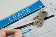 Signing a lease. With keys besides Royalty Free Stock Photos