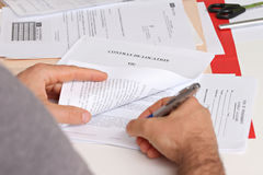 Signing a lease. Close-up hands of a man signing a lease or co-renting an apartment Royalty Free Stock Images