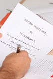 Signing a lease. Close-up hands of a man signing a lease or co-renting an apartment Royalty Free Stock Photos