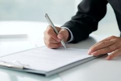 Signing legal document. Businessman signing legal document, selective focus Stock Photo