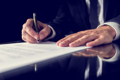 Signing legal document. Retro image of lawyer signing important legal document on black desk. Over black background