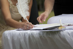 Signing of marriage certificate. Beautiful bride signing marriage certificate with feather pen Royalty Free Stock Photo