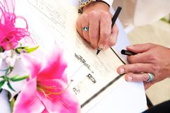 Signing the Marriage License. Mans hands holding pen and placing his signature as witness at the wedding on the marriage certificate license documentation Stock Photo