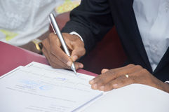 Signing of a married man. A newly married man puts his signature in the register book of the town hall of his town Royalty Free Stock Images