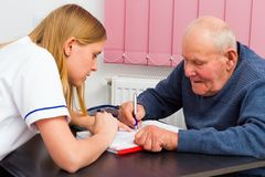 Signing Medical Papers. Elderly men signing medical papers at the doctor's office royalty free stock image