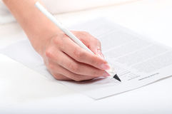 Signing a model release. On white table Royalty Free Stock Photo