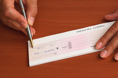 Signing a money cheque Stock Photos
