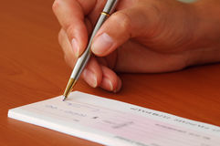 Signing a money cheque. Woman is signing a money cheque Stock Images