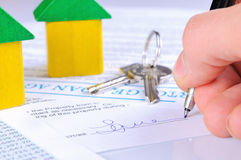 Signing the mortgage contract to delivery of keys with wooden ho. Uses front view Royalty Free Stock Images