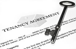 Signing a New Tenancy Agreement. A tenancy agreement waiting to be signed by a new tenant, with the key to the home resting on top Royalty Free Stock Photos