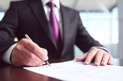 Signing Official Document. Businessman Signing An Official Document Royalty Free Stock Photos