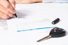 Signing pen and car key for Vehicle Sales Agreement.  Royalty Free Stock Image