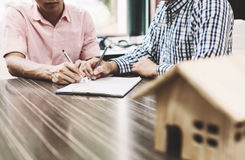 Signing of a real estate contract between buyer and broker. royalty free stock images