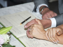 Signing register. Couple holding hands  whilst signing register Royalty Free Stock Image