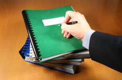 Signing A Report. Signing a business report on top af a pile of various reports Stock Image