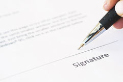 Signing Signature. A business person signing a contract Stock Image