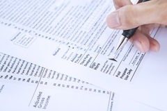 Signing tax form. Closeup of businessman hand filling out a 1040 tax form Stock Images