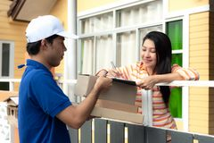 Signing to get her package. Delivery man holding a cardboard box woman putting signature in clipboard for shopping online. Signing to get her package. Delivery royalty free stock photography