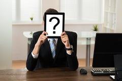 Signo de interrogación de Holding Board With del hombre de negocios Foto de archivo libre de regalías