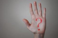 Signo de interrogación rojo en una mano Fotos de archivo