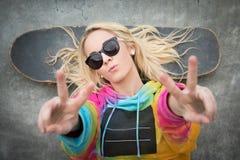 Signo de la paz de la muchacha del patinador Fotos de archivo libres de regalías