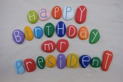 Signor President di buon compleanno con le pietre colorate sopra la sabbia bianca fotografie stock