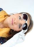 Signora abbastanza espressiva occhiali da sole d'uso dai pois di un bianco di vestito e sciarpa gialla nello studio Fotografie Stock