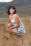 Signora abbastanza giovane sulle colline del prato Fotografia Stock