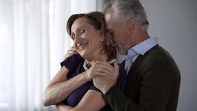 Signora abbracciante maschio anziana da dietro, entrambe sorridere, matrimonio armonioso fotografia stock libera da diritti
