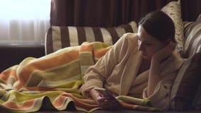 Signora in accappatoio beige con lo smartphone nel letto video d archivio