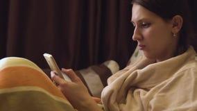 Signora in accappatoio beige con lo smartphone nel letto stock footage