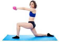 Signora adatta con le teste di legno che si inginocchia su una gamba Fotografia Stock Libera da Diritti