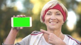 Signora adulta allegra che indica allo smartphone con lo schermo verde e che sorride, app fotografie stock