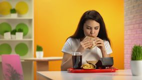 Signora affamata che gode del gusto dell'hamburger, cena in fast food, appetito archivi video