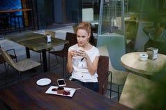 Signora affascinante che pensa a qualcosa mentre godendo dello svago durante la prima colazione di mattina nella barra accoglient Immagine Stock Libera da Diritti