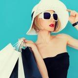 Signora affascinante di estate di acquisto su fondo blu fotografia stock