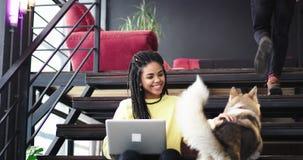 Signora africana carismatica che lavora al suo computer portatile che si siede sulle scale, dietro il suo un uomo per sollevare l archivi video