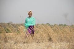 Signora africana che cammina nel campo fotografia stock libera da diritti