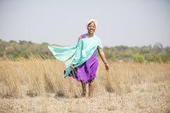 Signora africana che cammina nel campo immagine stock