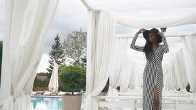 Signora afroamericana elegante in vestito da cocktail a strisce e posa black hat vicino allo stagno nel fondo dell'albergo di lus archivi video