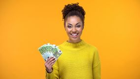 Signora afroamericana sorridente che mostra mazzo di euro alla macchina fotografica, lavoro pagato caro fotografia stock libera da diritti