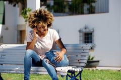 Signora afroamericana sorridente che si siede su un banco e che fa una telefonata all'aperto Immagine Stock