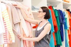 Signora alla moda che seleziona abbigliamento in boutique Fotografia Stock