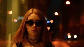 Signora alla moda con i capelli di scarsità in vetri gira intorno alla città nella sera archivi video