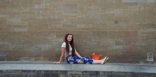 Signora alla moda con la corona del fiore che si siede sulla parete fotografie stock libere da diritti