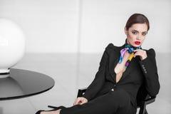 Signora alla moda di affari in vestito nero nell'interno minimalistic Immagini Stock
