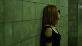 Signora alla moda in occhiali da sole che posano per la macchina fotografica nel sottopassaggio stock footage