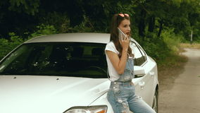 Signora alla moda parla sul telefono cellulare mentre sta vicino alla sua automobile video d archivio