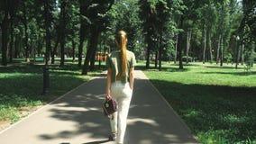 Signora alla moda sexy cammina al parco stock footage